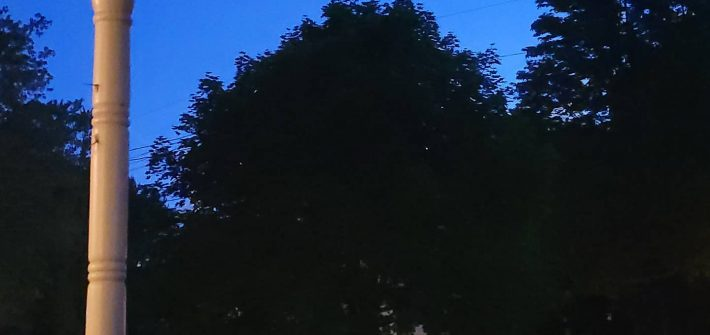 A blue sky at nightfall. Tree silhouettes appear in the foreground with a glimpse of a porch to the left.